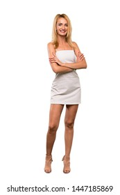 A full-length shot of a Young blonde woman keeping the arms crossed in frontal position over isolated white background