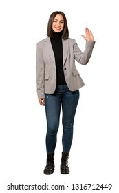 A full-length shot of a Young business woman saluting with hand with happy expression over isolated white background
