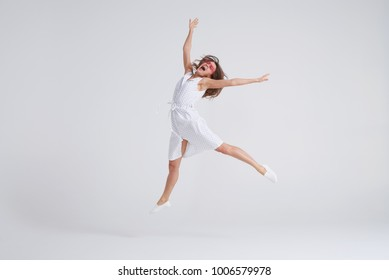 Full-length shot of young charming female in dress jumping over white background