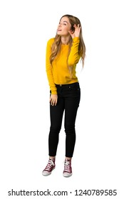 A full-length shot of a young girl with yellow sweater listening to something by putting hand on the ear on isolated white background