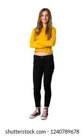 A full-length shot of a young girl with yellow sweater keeping the arms crossed in frontal position on isolated white background