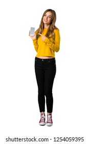 A full-length shot of a young girl with yellow sweater showing the mobile on isolated white background