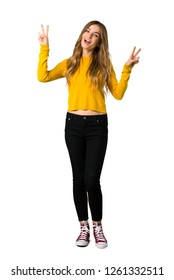 A full-length shot of a young girl with yellow sweater smiling and showing victory sign with both hands on isolated white background
