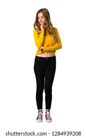 A full-length shot of a young girl with yellow sweater looking down with the hand on the chin on isolated white background