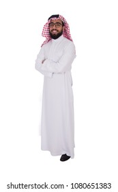 Full-length shot of young khaleeji man wearing shemagh and thobe standing crossed arms smiling isolated on a white background.