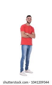 A full-length shot of a young man standing with a crossed arms in a casual outfit, isolated on a white background.