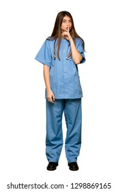 Full-length shot of Young nurse showing a sign of silence gesture putting finger in mouth on isolated white background