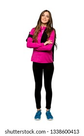 Full-length shot of Young sport woman keeping the arms crossed in frontal position over isolated white background