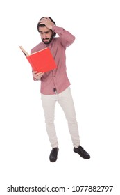 Full-length shot of a young student holding an open book looks exhausted putting a hand on the head, isolated on a white background.