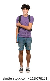A full-length shot of a Young student man keeping the arms crossed in frontal position over isolated white background