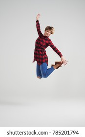 Full-length shot of young woman in checked shirt and jeans jumping at studio