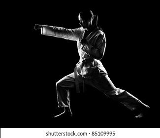 full-length silhouette portrait of beautiful martial arts girl in kimono exercising karate kata on black