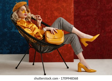 Full-length studio fashion portrait of elegant woman wearing yellow color sunglasses, beret, silk blouse, houndstooth printed trousers, pointed toe shoes, posing on chair, holding stylish leather bag  - Shutterstock ID 1709948368