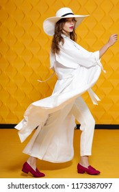Full-length studio fashion portrait of young beautiful model wearing long white trench coat, trousers, wide-brimmed hat, loafers, posing on yellow background