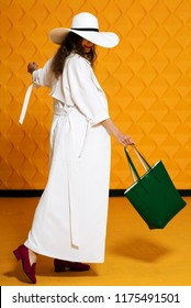 Full-length studio fashion portrait of young beautiful model wearing long white trench coat, wide-brimmed hat, pink loafers, holding green faux-leather shopper bag, posing on yellow background