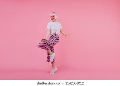 Full-length studio shot of lovely girl dancing in white sneakers. Indoor portrait of pleased caucasian lady in pink peruke and trendy pants.