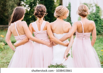 full-length three bridesmaids in powder dresses transformers and hug a bride in a white dress with a wedding bouquet in her hand on a green lawn