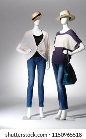 full-length two mannequin in female shirt with blue jeans, ,hat, handbag ,sunglasses–light background
