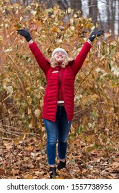 Full-length vertical photo of pretty smiling young woman with long blond hair wearing red puffy winter coat looking up while throwing dry leaves over her head