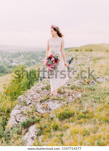 Full-length view of the pretty bride with the huge wedding bouquet looking aside while standing on the mountains.