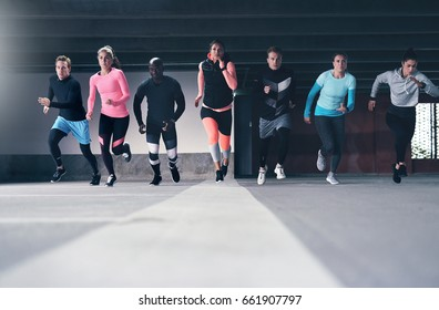 Full-length view of runners moving towards camera during race indoors. Copyspace
