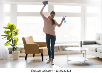 Full-length woman in casual clothes dance do house cleaning holds blue rag spray bottle detergent feels happy, qualified housekeeping specialist agency hiring, quick fast and easy home chores concept