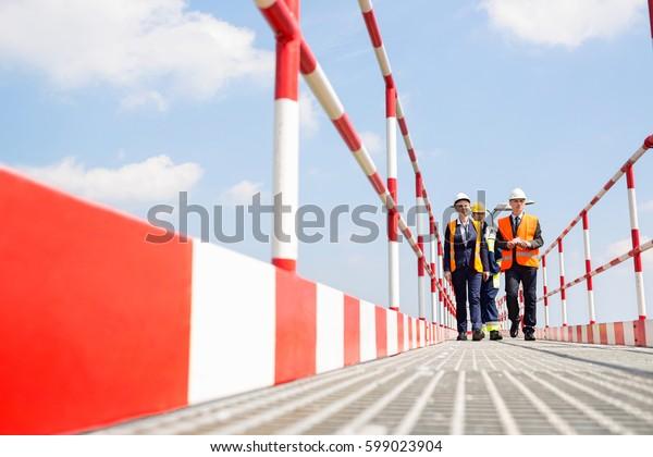 Full-length of workers walking on footbridge against sky