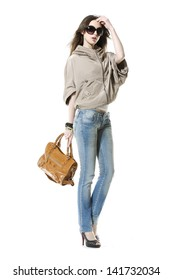 full-length young girl in jeans with sunglasses holding bag posing on white background