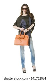 full-length young girl in jeans with sunglasses holding bag posing