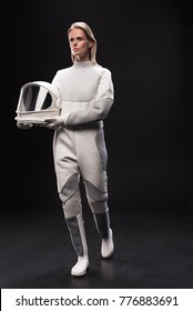Full-length of young spacewoman wearing protective costume is going ahead and looking aside wistfully while holding her helmet. Isolated background. Cosmos concept