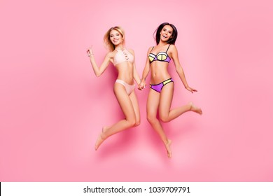 Full-size, full length portrait of attractive, charming, pretty, dreamy, playful brunette, stylish, slim, fit ladies, tourists in swim suits jumping over pink background, blonde showing v-sign