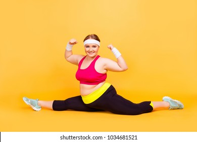 Full-size photo of cheerful excited confident funny plump woman wearing sportive clothes, she is doing splits on the floor and showing muscles on upper arms, isolated on yellow background