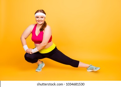 Full-size photo of funny cheerful plump positive person with flabby body using sweat-band, bracers, she is warming up her legs and feet before morning jogging, isolated on bright yellow background