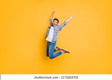 Full-size portrait of happy excited young man screaming and jumping up with raised fists celebrate the victory isolated on vivid yellow background