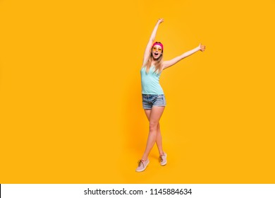 Full-size portrait of young blondy girl in a pink cap stand holding her hands up isolated on bright yellow background with copy space for text