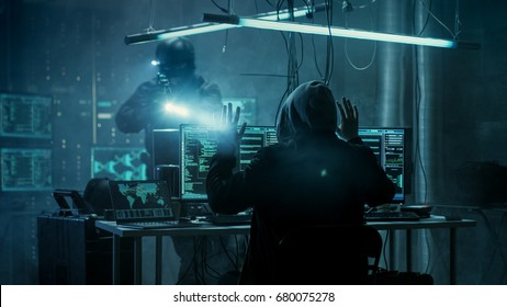 Fully Armed Special Cybersecurity Forces Soldier Arrests Highly Dangerous Hooded Hacker. Hideout is Dark and Full of Computer Equipment.