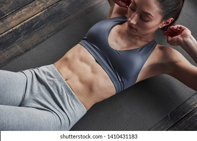 Fully concentrated. Top view of girl with slender body works on the abs when lying on the floor.