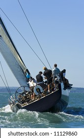 A fully crewed racing yacht catching the wind