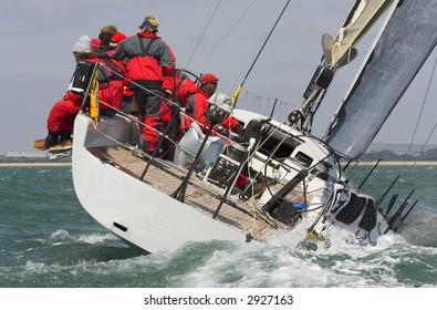 A fully crewed racing yacht racing hard and leaving a big wake