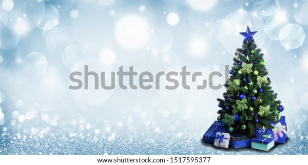 Fully decorated christmas tree with blue and green baubles and bows and presents on glitter bokeh background