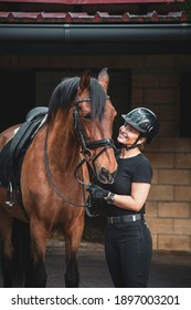 Fully equipped female rider with helmet and black suit in front of a stable with her brown horse looking into her eyes and smiling
