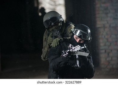 Fully equipped military men with automatic weapons playing in  airsoft strikeball