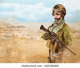 Fully equipped military soldier woman with red lacquer nails holding an automatic rifle M16 on desert background.