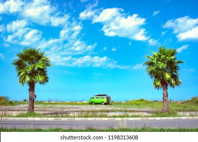 Fully equipped old timer camper van parked on the beautiful long beach between two palm trees on a bright sunny summer day