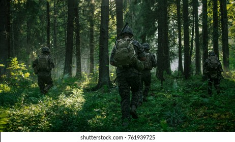 Fully Equipped Soldiers Wearing Camouflage Uniform Attacking Enemy, Rifles Ready to Shoot. Military Operation in Action, Squad Running in Formation Through Dense Smokey Forest. Back View Footage.