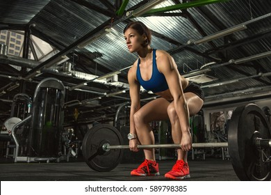 Fully focused. Low angle full length shot of a beautiful young fit and toned fitness woman with strong athletic body doing heavy weightlifting workout with a barbell at the gym