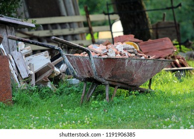Fully Loaded With Construction Material Rusted Used Wheelbarrow  Construction Cart With Missing Tyre Surrounded With Broken