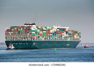 Fully loaded large cargo container ship in the North Sea by day. Transportation and shipping.