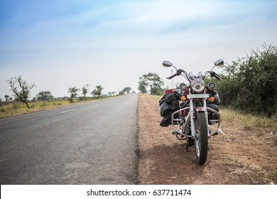 A fully packed motorcycle next a long empty road.