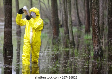 fully protected in uniform,boots,gloves and mask technician examining sample of water in plastic container in floods area